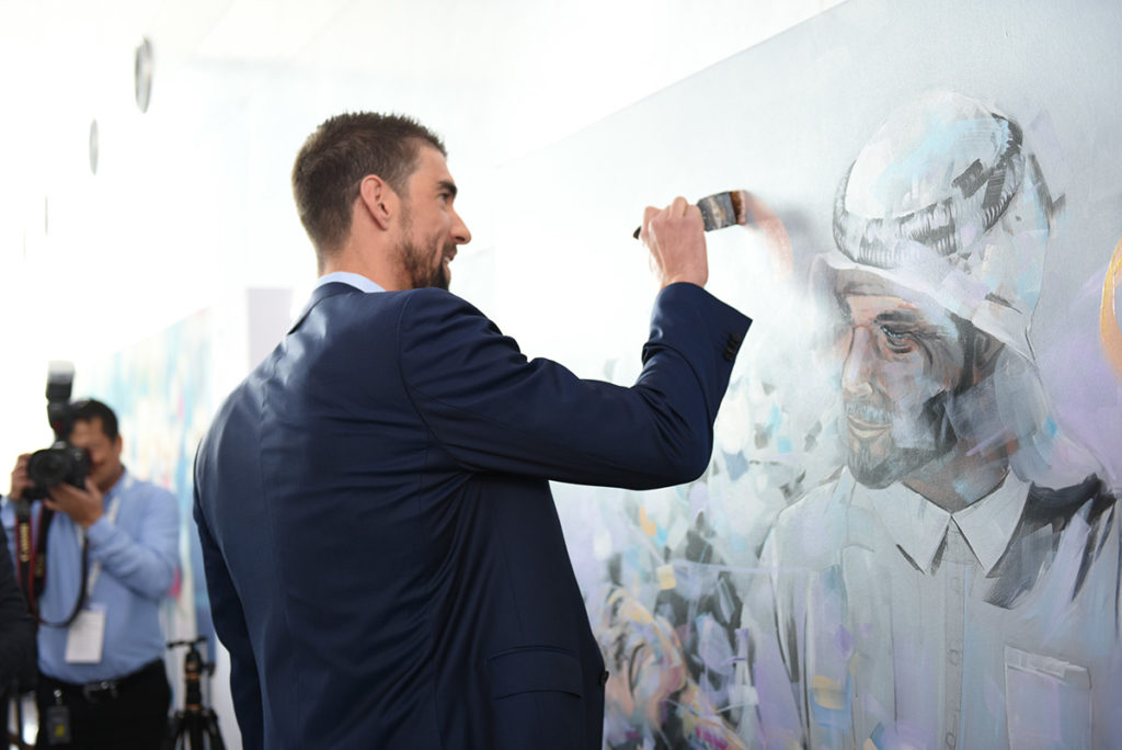 MIchael Phelps adding a brush stroke to a Painting by Artist Dairo Vargas